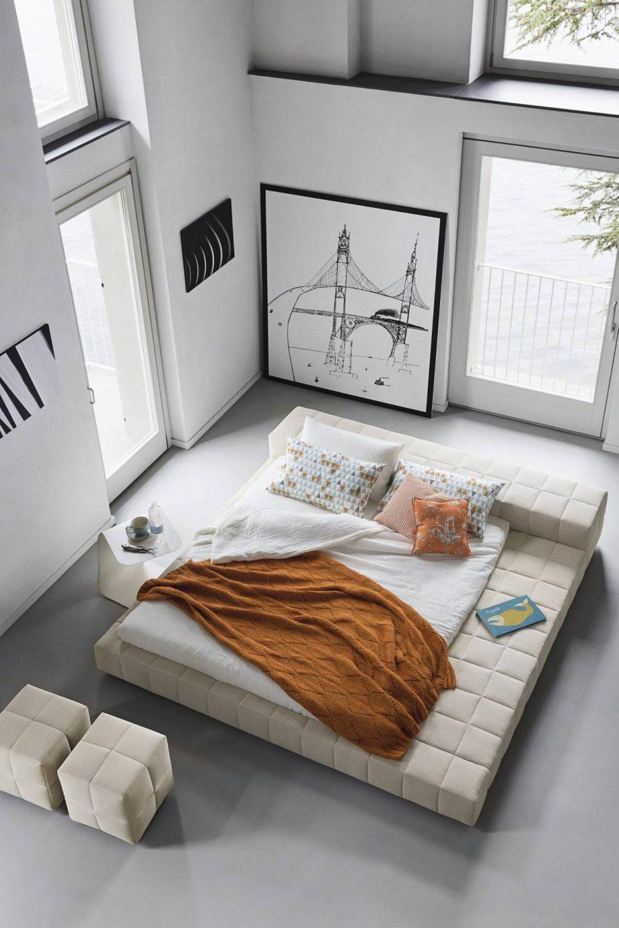 Chiếc giường thấp này có nền được bọc nệm để tạo tính thẩm mỹ nhẹ nhàng hơn