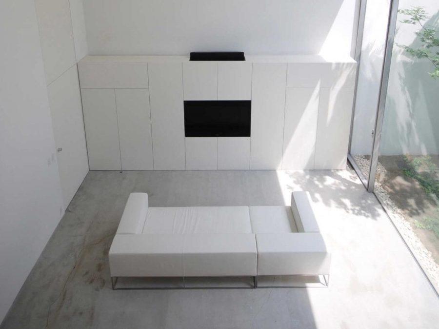 Dựa trên nền bê tông, đặc điểm duy nhất của phòng khách tối giản này là một chiếc TV màu đen