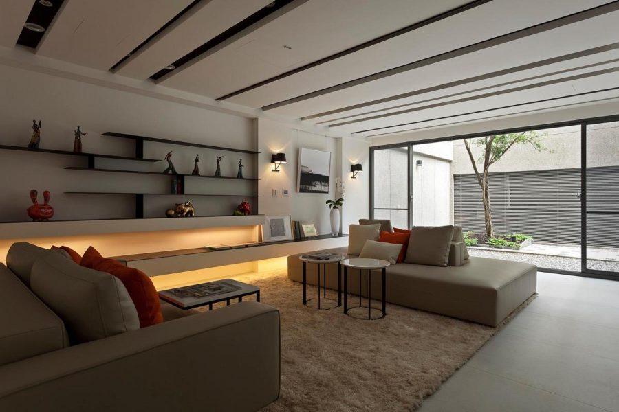 Phòng khách hiện đại theo phong cách Châu Á tối giản này sử dụng màu đỏ nổi bật để thu hút ánh nhìn vào chỗ ngồi khối thư giãn, giá đỡ màu đen thông minh và lò sưởi đèn LED
