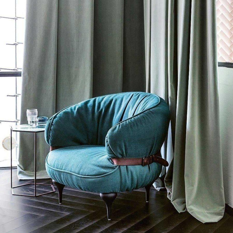 Một chiếc ghế bành sang trọng màu xanh lục với chân ghê nhỏ. Điểm nhấn của chúng là phía mặt sau của ghê được thắt dây lưng cực ấn tượng