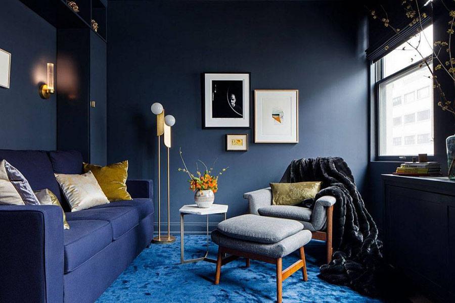 Phòng khách hiện đại tuyệt đẹp với bức tường màu xám đậm, thảm màu xanh lam và sofa màu xanh lam đậm.